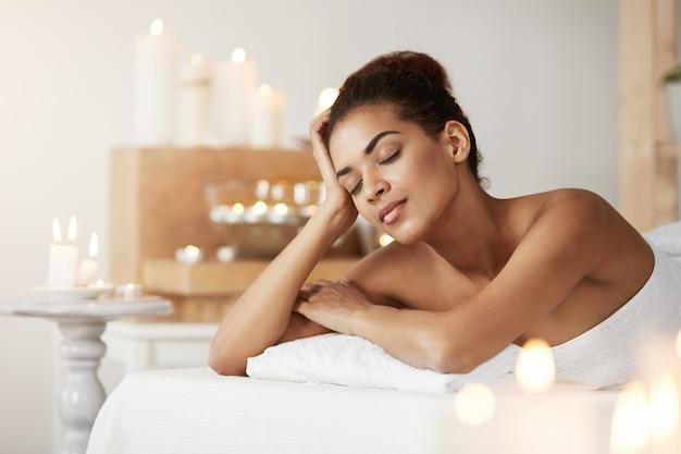 Linda mulher africana descansando relaxante no salão spa