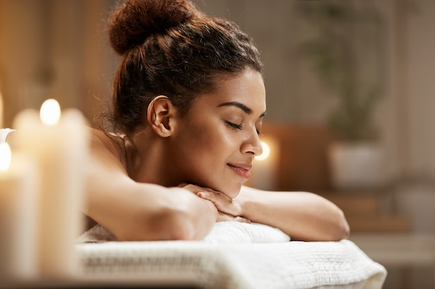 Linda mulher africana descansando relaxante no spa resort com os olhos fechados.