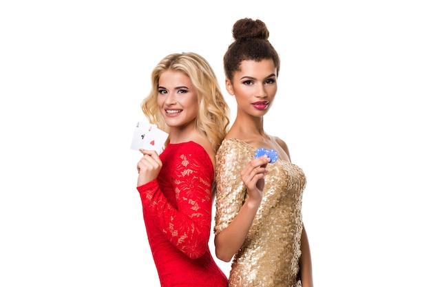 Linda mulher africana e jovem branca com cabelo loiro longo claro em roupa de noite. segurando cartas de jogar e fichas. isolado. pôquer