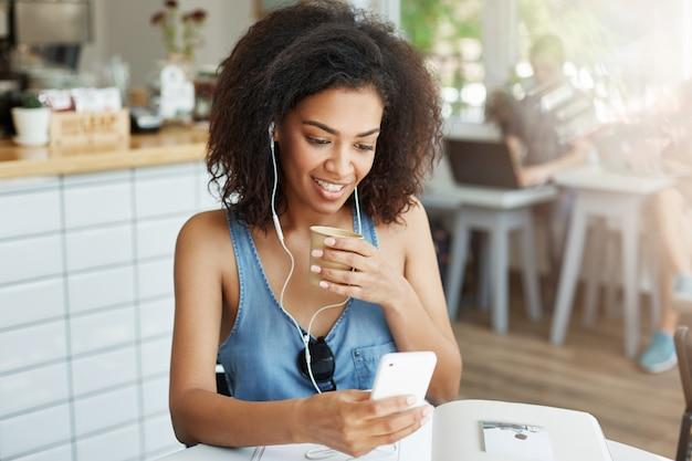 Linda mulher africana em fones de ouvido, sorrindo, olhando para a tela do telefone, bebendo café sentado descansando no café.