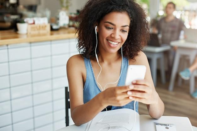 Linda mulher africana em fones de ouvido, sorrindo, olhando para a tela do telefone sentado descansando no café.
