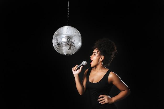 Linda mulher africana em pé com uma bola de discoteca prateada isolada sobre o espaço negro, segurando um microfone