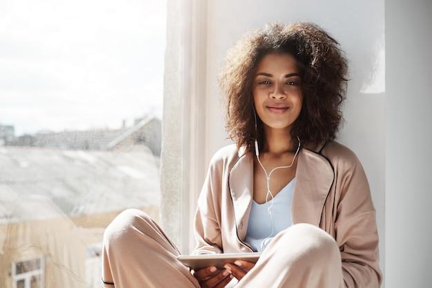 Linda mulher africana em roupa de noite e fones de ouvido sorrindo segurando a tablet sentado no peitoril da janela.