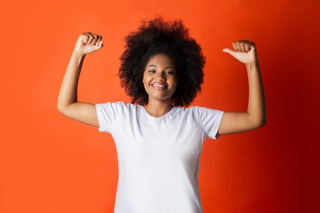 Linda mulher africana em uma camiseta branca com os braços erguidos em fundo vermelho
