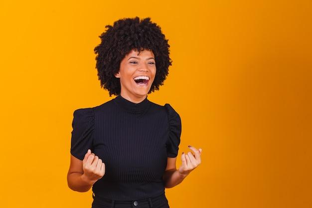 Linda mulher africana feliz e animada, expressando gesto vencedor. bem-sucedido e comemorando a vitória, triunfante, interno
