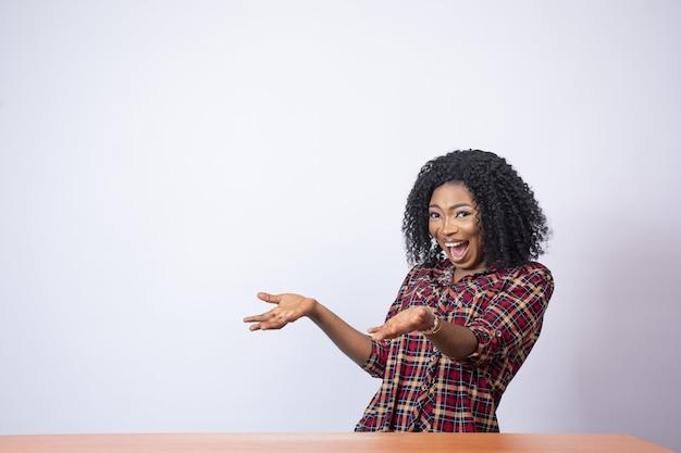 Linda mulher africana gesticulando para o espaço vazio ao seu lado com empolgação