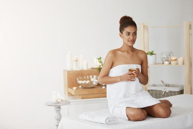 Linda mulher africana na toalha sorrindo segurando vidro com chá sentado no salão spa.