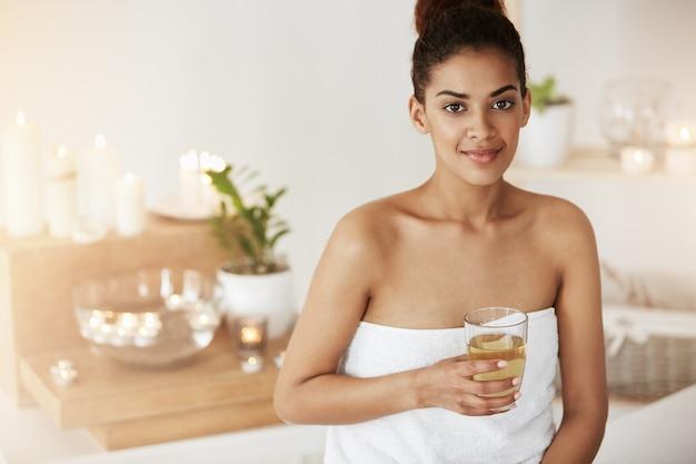 Linda mulher africana na toalha sorrindo segurando vidro.