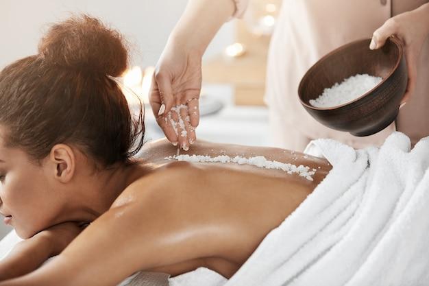 Linda mulher africana relaxante desfrutando spa saúde massagem com sal marinho.