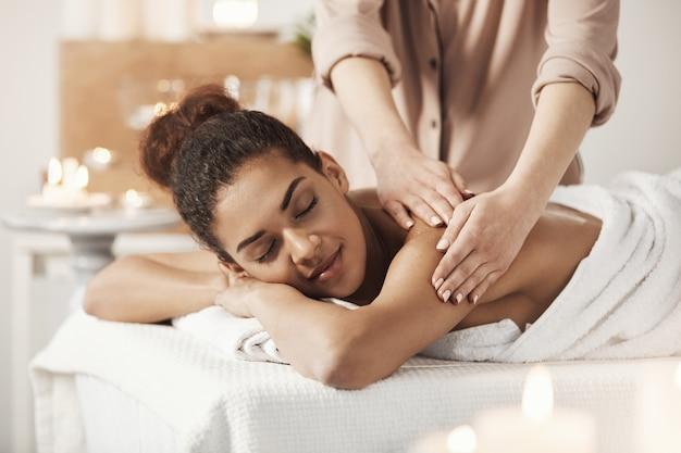 Linda mulher africana sorrindo desfrutando de massagem com os olhos fechados no salão spa.