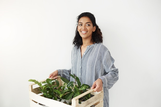 Linda mulher africana sorrindo segurando a caixa com plantas.