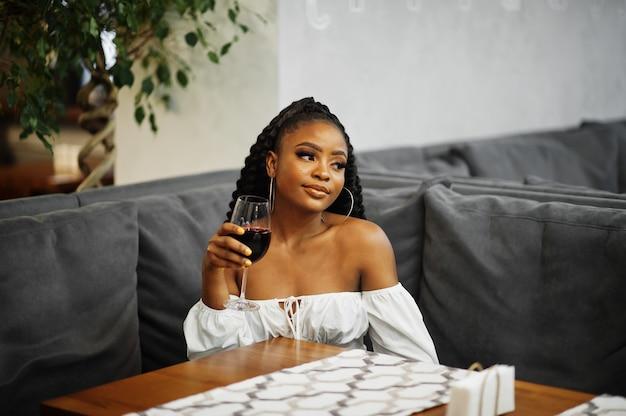 Linda mulher afro-americana com blusa branca e calça de couro vermelho posar no restaurante com um copo de vinho.