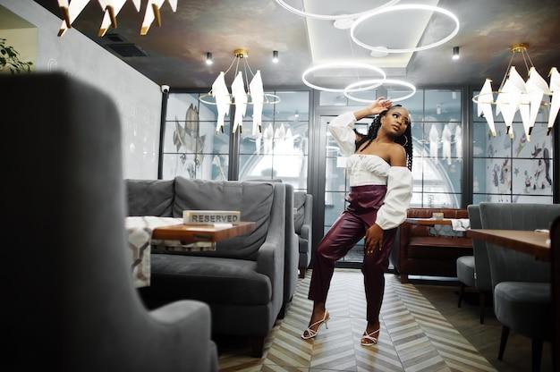 Linda mulher afro-americana com blusa branca e calças de couro vermelho pose no restaurante.
