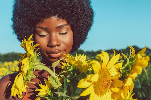 Linda mulher afro-americana com cabelo encaracolado estilo afro em um campo de girassóis.