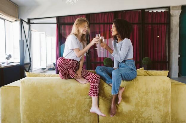 Linda mulher afro-americana com cabelo escuro e encaracolado e uma linda mulher com cabelo loiro sentada no sofá segurando taças de champanhe nas mãos enquanto passam um tempo juntos em casa.
