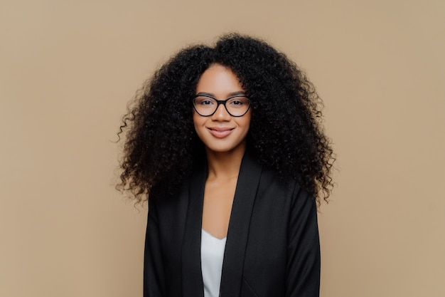 Linda mulher afro-americana com cabelos nítidos, vestida com elegante jaqueta preta, óculos transparentes