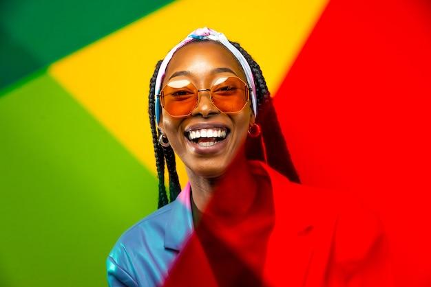 Linda mulher afro-americana com penteado afro de tranças e roupas elegantes - retrato de uma jovem negra em estúdio