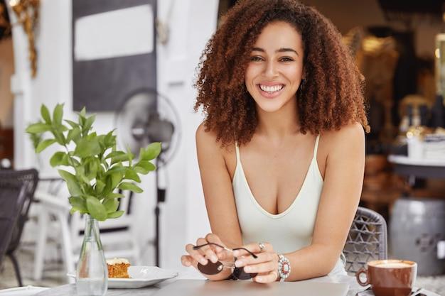 Linda mulher afro-americana com um sorriso largo e agradável descansando sozinha em um café na calçada, aproveitando um bom descanso durante as férias de verão
