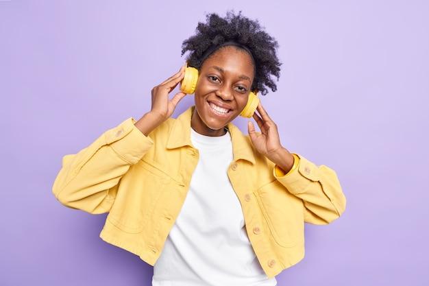Linda mulher afro-americana de pele escura positiva com sorriso cheio de dentes ouve música por meio de fones de ouvido sem fio e desfruta do tempo livre inclina a cabeça