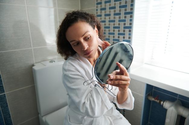 Linda mulher afro-americana em roupão de banho olha seu reflexo no pequeno espelho cosmético ao usar a massagem gua-sha para massagem facial de drenagem linfática. conceitos de cuidados com a pele
