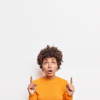 Linda mulher afro-americana impressionada parece chocada acima indica no espaço da cópia mostra incrível oferta surpreendida por grandes vendas usa roupas casuais isoladas sobre parede branca. promoção