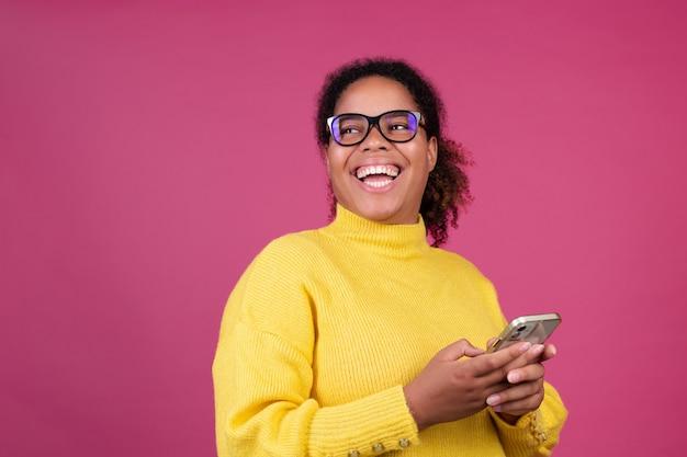 Linda mulher afro-americana na parede rosa digitando mensagem no celular animada, feliz