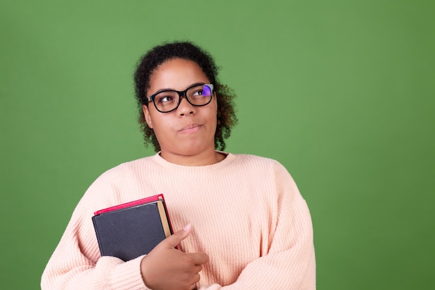 Linda mulher afro-americana na parede verde com notebooks aluno professor usando óculos, olhar pensativo de lado