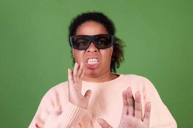Linda mulher afro-americana na parede verde com óculos de cinema 3d assistindo filme emoção de nojo