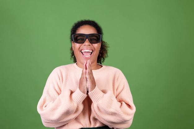 Linda mulher afro-americana na parede verde com óculos de cinema 3d feliz, alegre positiva
