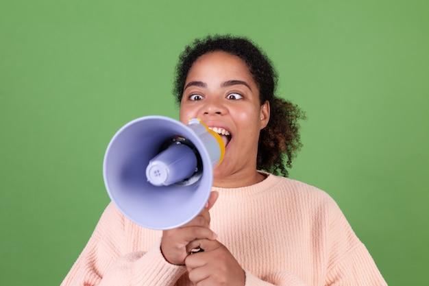 Linda mulher afro-americana na parede verde gritando e gritando no megafone, pedindo atenção