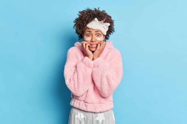 Linda mulher afro-americana preocupada com cabelo encaracolado olha nervosamente para a câmera, vestida com pijamas e usa máscara de dormir na testa isolada sobre a parede azul
