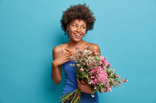 Linda mulher afro-americana romântica encantadora segurando um grande buquê e recebendo flores
