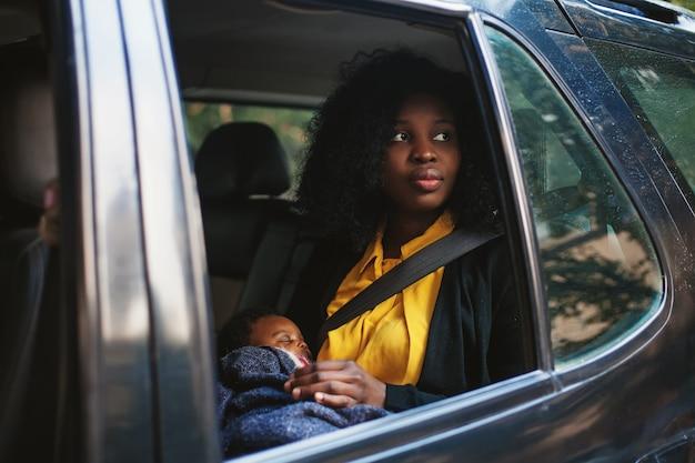 Linda mulher afro-americana segurando um bebê no banco de trás do carro