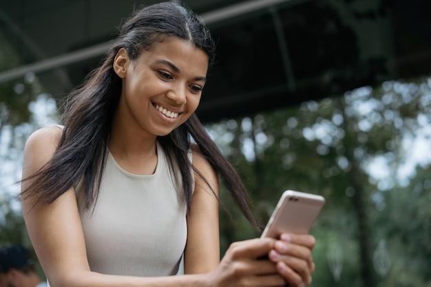 Linda mulher afro-americana sorridente, usando a comunicação do celular, assistindo a um filme online sentado ao ar livre