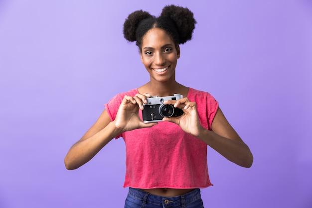 Linda mulher afro-americana sorrindo e segurando uma câmera retro, isolada