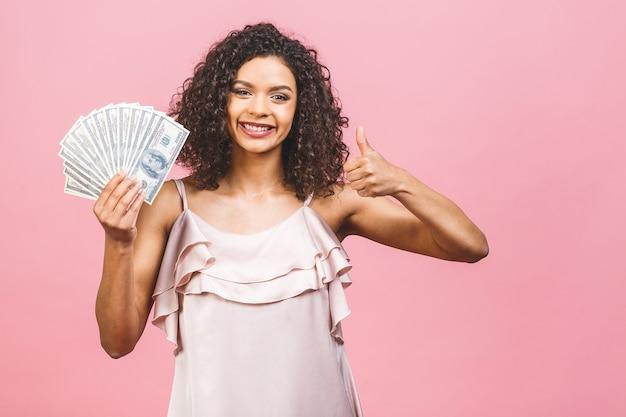 Linda mulher afro-americana surpresa num vestido segurando dinheiro