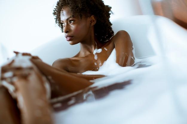 Linda mulher afro-americana tomando banho em uma banheira cheia de espuma