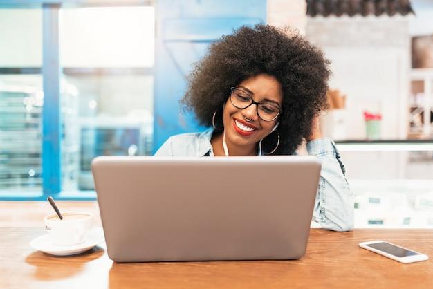 Linda mulher afro-americana usando celular e laptop no café. conceito de comunicação.