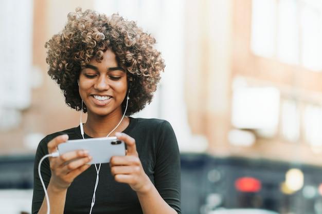 Linda mulher afro-americana usando fones de ouvido na cidade remixada de mídia