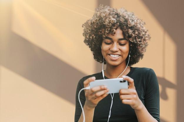 Linda mulher afro-americana usando smartphone com mídia remixada de gráfico de sombra de janela