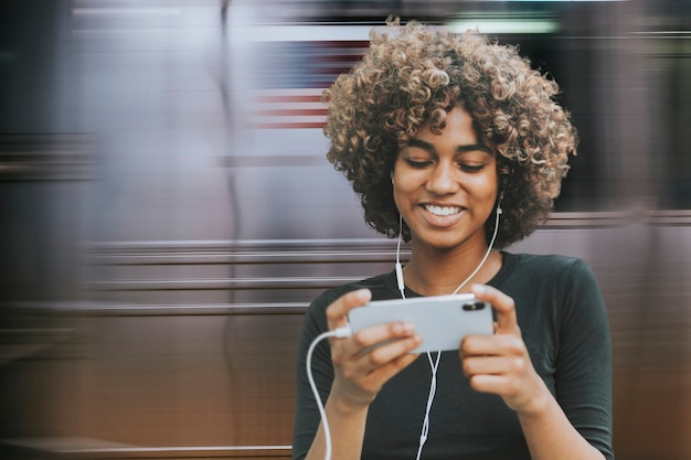Linda mulher afro-americana usando smartphone na mídia remixada do metrô