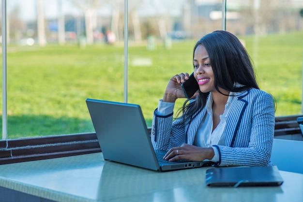 Linda mulher afro-americana usando um laptop e falando em seu telefone celular