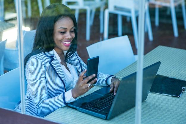 Linda mulher afro-americana usando um laptop e olhando para o celular atrás de uma janela