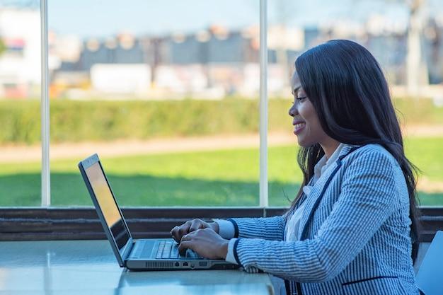 Linda mulher afro-americana usando um laptop