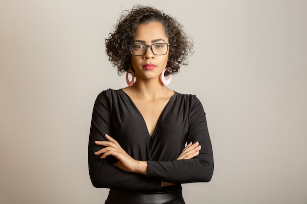 Linda mulher afro com expressão séria de óculos e com os braços cruzados