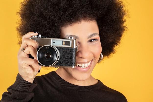 Linda mulher afro com uma câmera fotográfica antiga