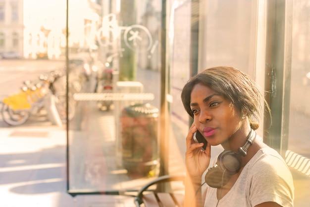 Linda mulher afro falando em um smartphone