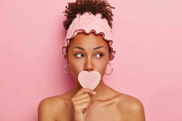 Linda mulher afro mantém a pele em boas condições, tenta relaxar e se desestressar, remove a sujeira do dia a dia com esponja cosmética, desvia o olhar, usa bandana de chuveiro rosa e brincos redondos