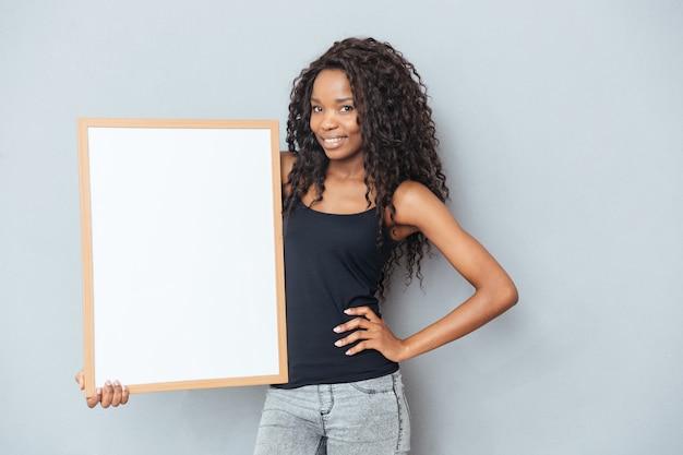 Linda mulher afro mostrando um quadro em branco sobre uma parede cinza