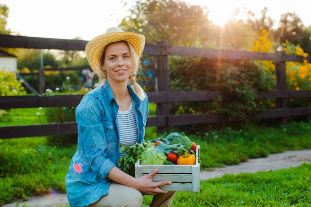 Linda mulher agricultora no chapéu com caixa de legumes ecológicos frescos